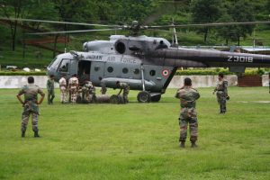 IAF helicopter getting loaded with flood relief stores for dropping in affected areas. IAF airmen loading the aircraft.