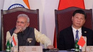 Indian Prime Minister Narendra Modi and Chinese President Xi Jinping sitting in a formal event with faces away from each other.
