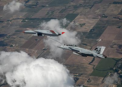 F/A - 18  gets refuelled by a Boeing MQ-25